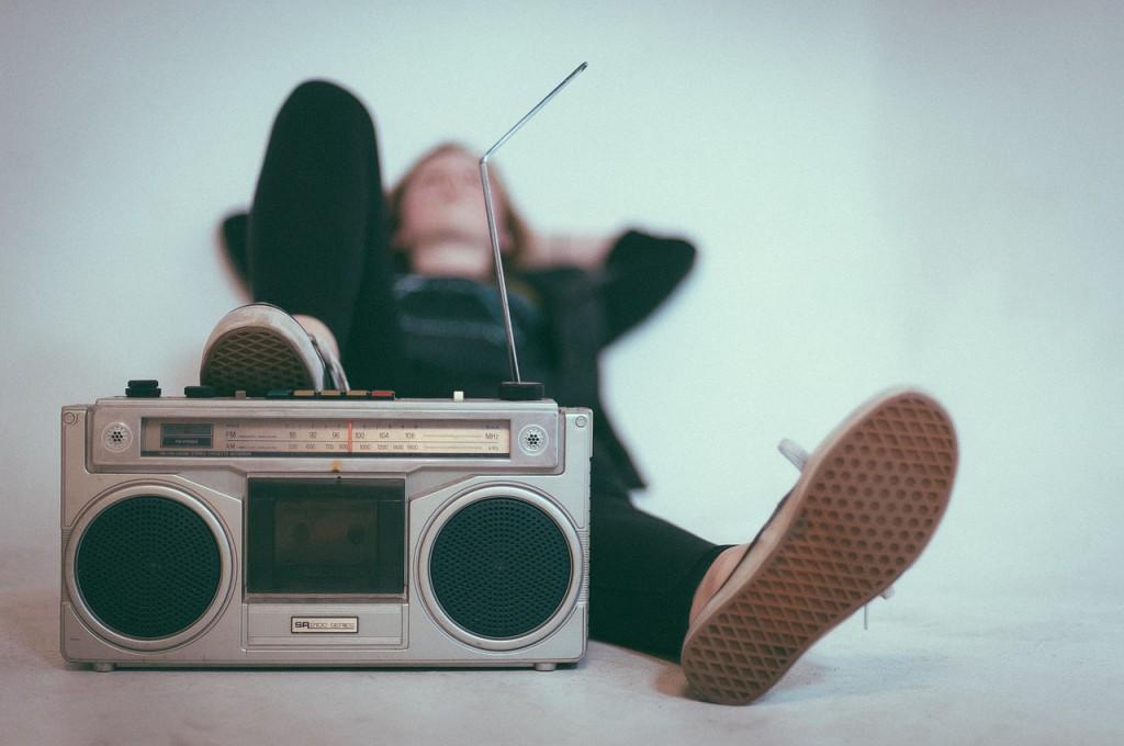 Ein Mieter liegt neben einer Box und hört Hausmusik